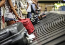 Bright red suit ace on a luggage conveyor belt at the luggage claim in an airport.Thailand-Property.com