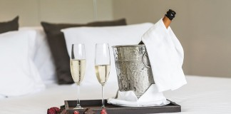 Champagne and chocolate on white sheets in a hotel.Thailand-Property.com
