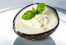 Delicious coconut ice cream in a coconut shell set on a white plate with fresh mint leaf. Thailand-Property.com