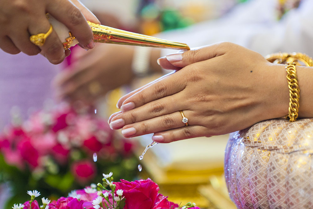 Photo of a Thai bride receiving holy water from her elders. Thailand-Property.com