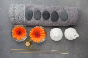 Spa massage setting with rolled towel, thai herbal compress balls and flowers. Flat lay. Top view