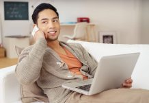 A man is calling while relaxing in his new condominium