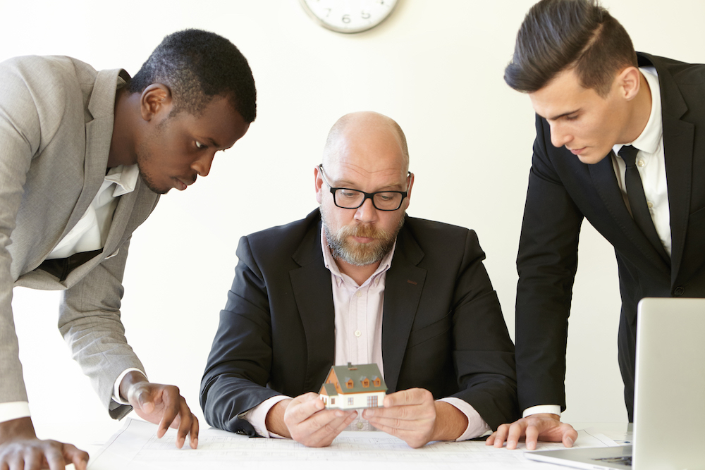 Caucasian boss in glasses holding scale model house of future real estate while two young architects presenting construction project to him. Team of engineers having brainstorm session in office