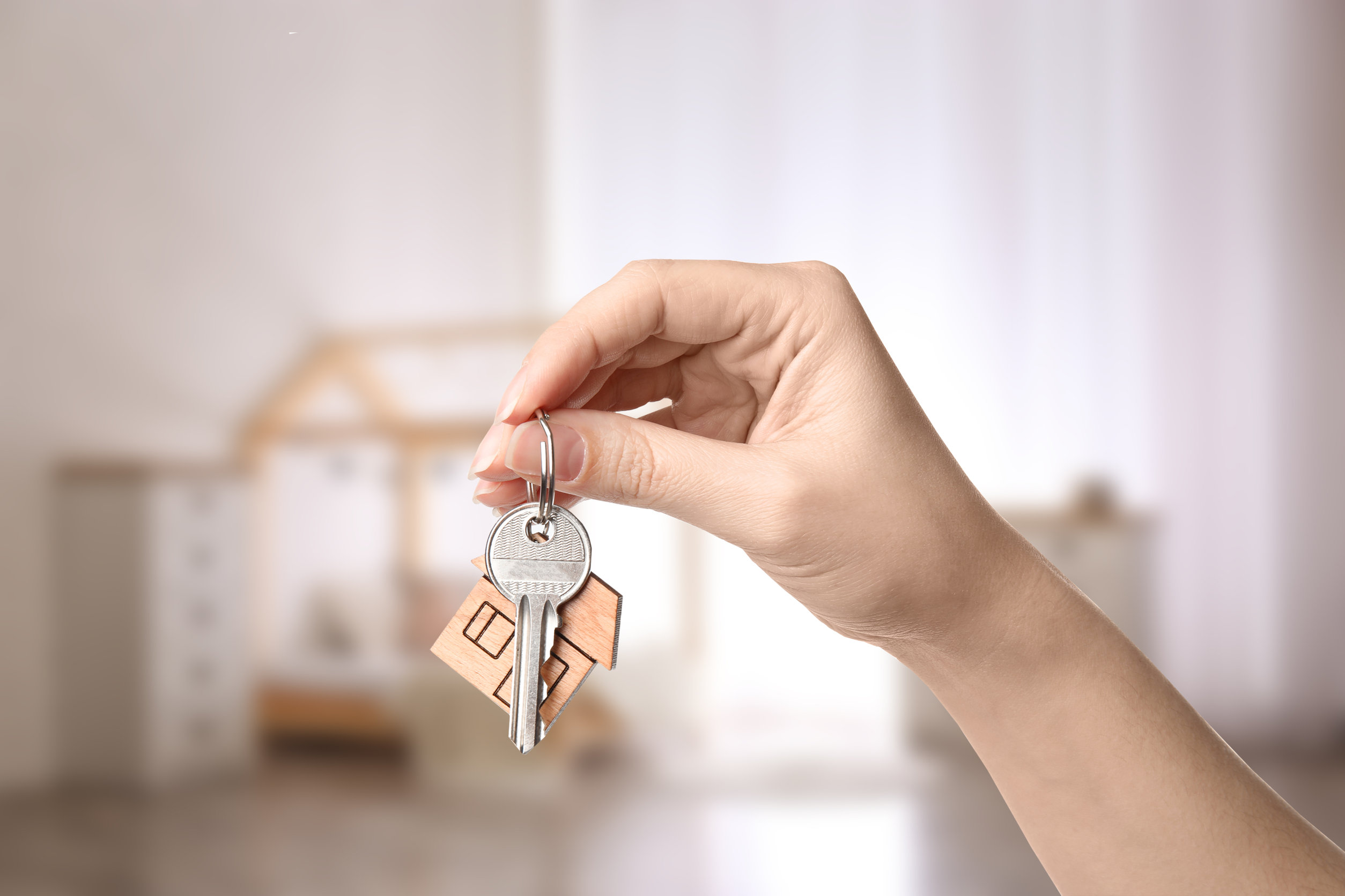 Woman holding house key on blurred background, closeup