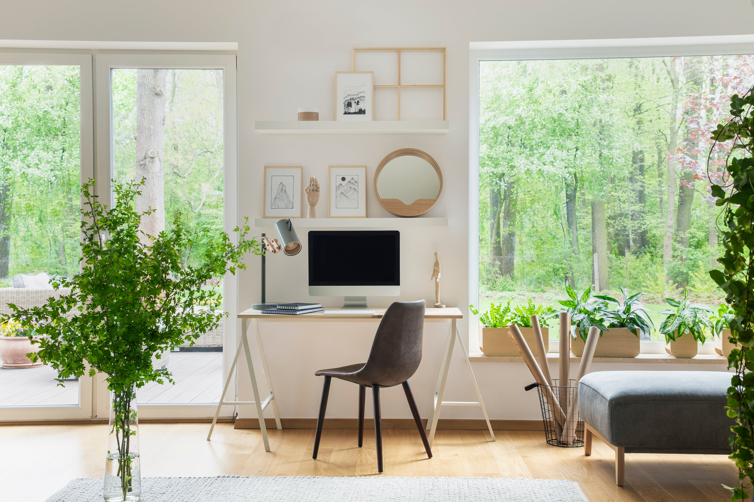 Grey chair at desk with desktop computer in scandi open space in